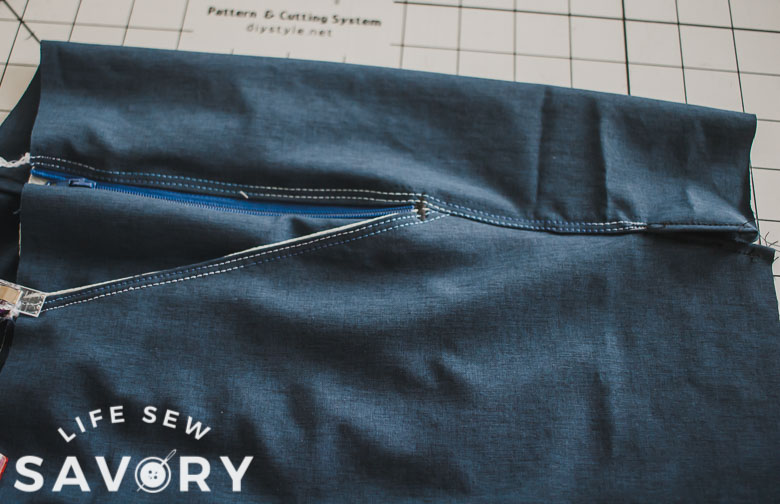 top stitch side seams to back, zig zag bottom of pocket to secure